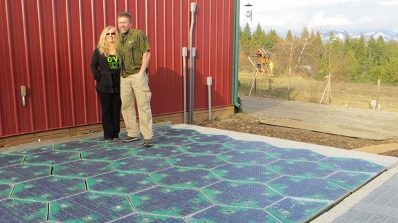 Scott and Julie Brusaw stand with their solar panel tiles inthe prototype parking space. Image: Solar Roadways