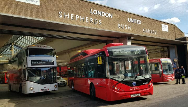 Picture of one of the first new electric buses leaving a bus garage in Shepherd's Bush.