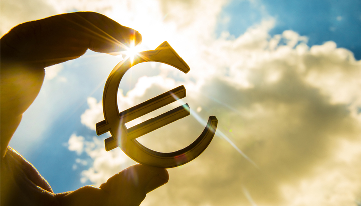 Image of euro sign being held by two fingers against a backdrop of the sky and clouds