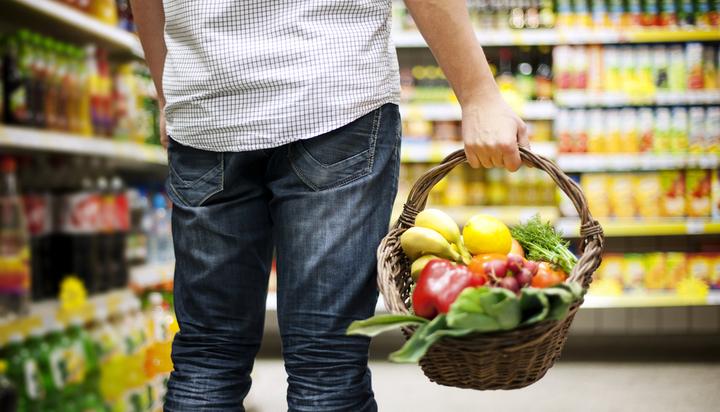 Man holding basket of fruit and vegetables in a supermarket