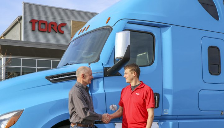 Daimler Trucks North America CEO Roger Nielsen, left,, shakes hands with Torc CEO, Michael Fleming